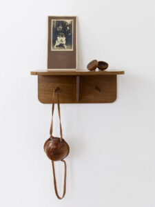 Replica of vintage shelf with an antique family photo and handcarved wooden objects lemon and respirator mask